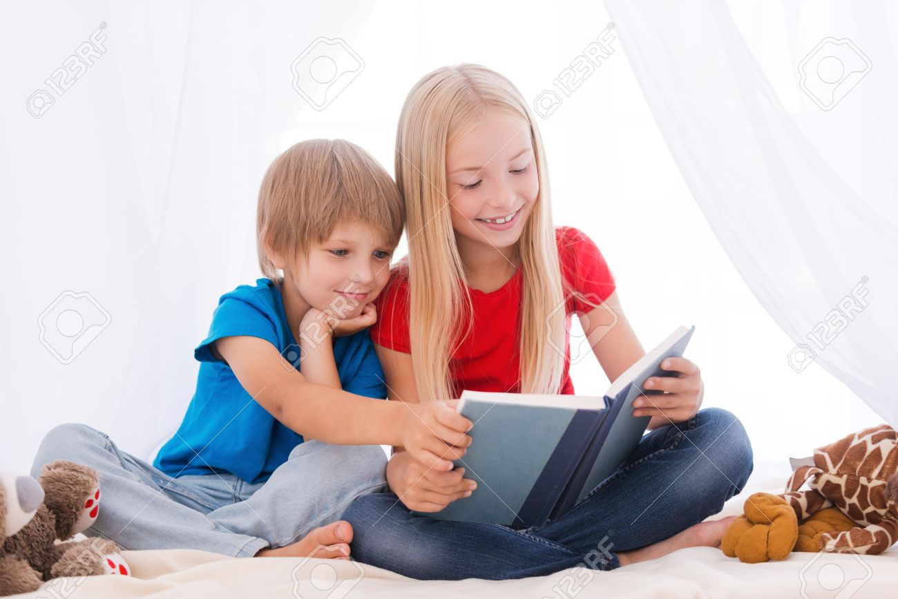 reading an exciting book. two cute children reading book together