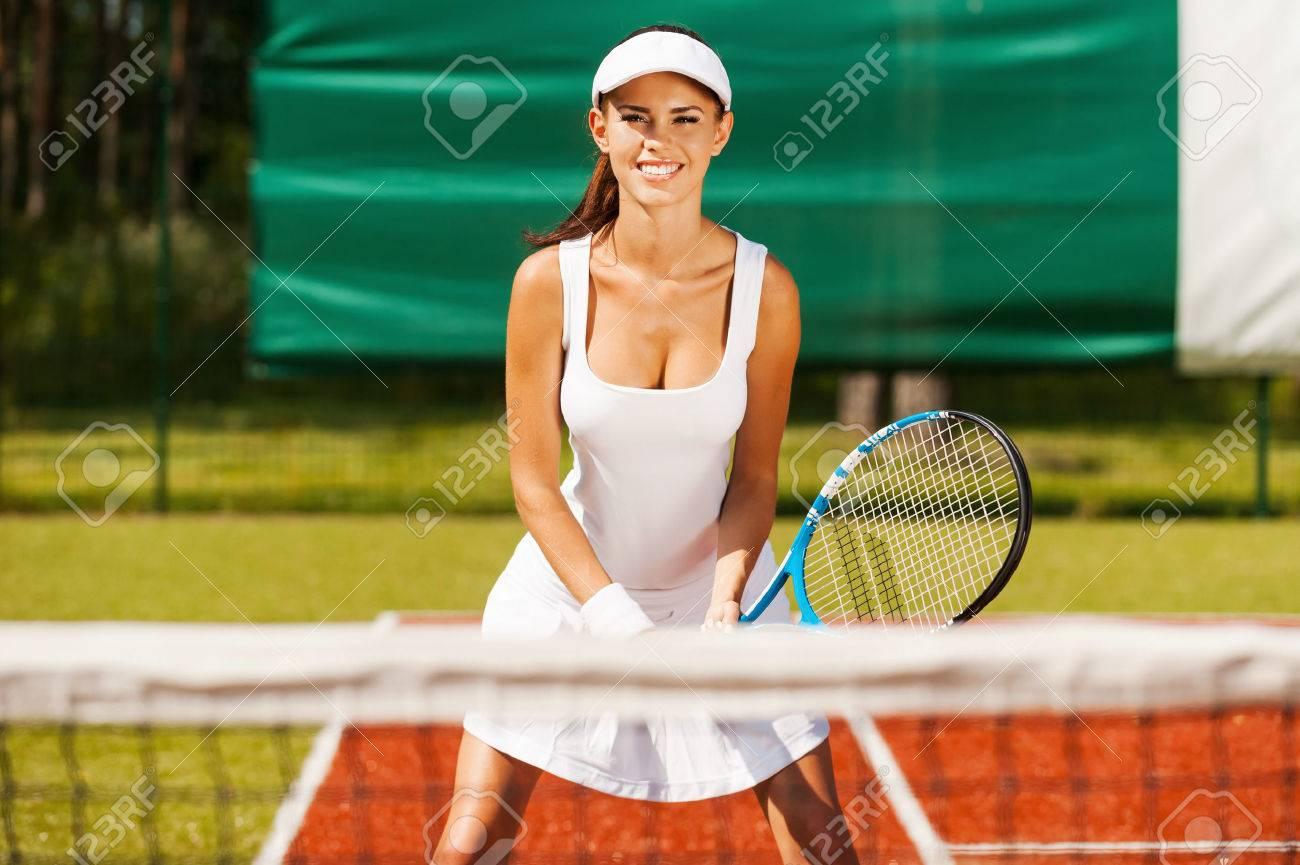 En liquidación nueva colección sombras de Estoy listo para jugar! Joven y bella mujer en ropa deportiva jugando al  tenis mientras está de pie en la cancha