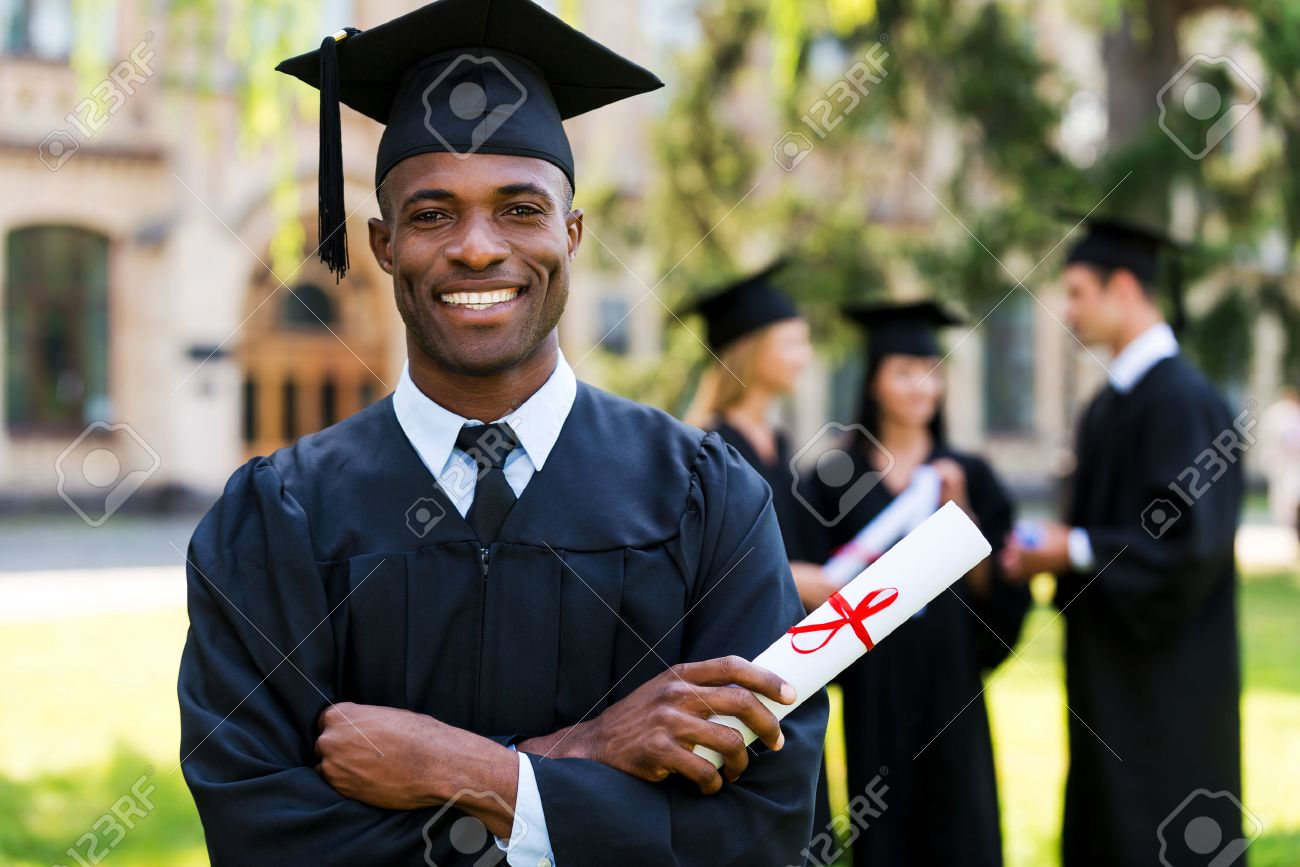 Happy Graduate. Happy African Man In Graduation Gowns Holding ...