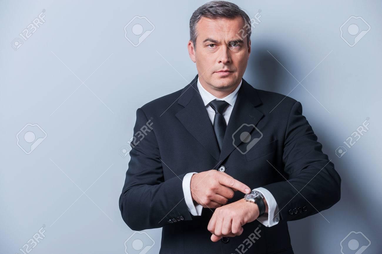 maduro tiempo cámara es la señalando y está mientras a el mirando dineroHombre en formal confía El reloj pie fondo ropa su de gris contra lKJTFc1