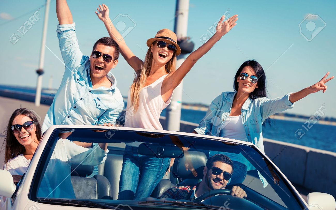 Friends in convertible. Group of young happy people enjoying road trip in their white convertible and raising their arms - 32368228