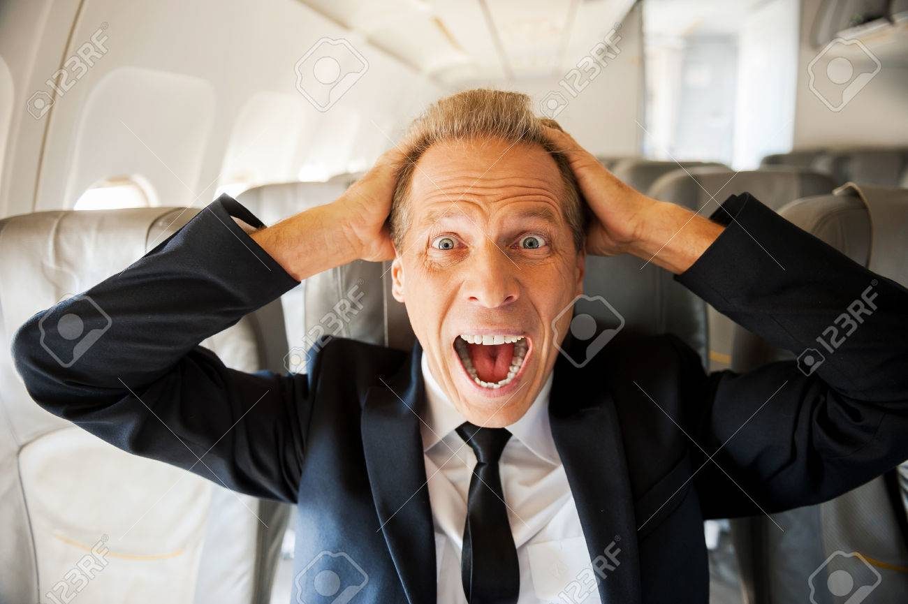 Fear of flight. Shocked mature businessman touching his head with hands and looking at camera while sitting at his seat in airplane Stock Photo - 33010598