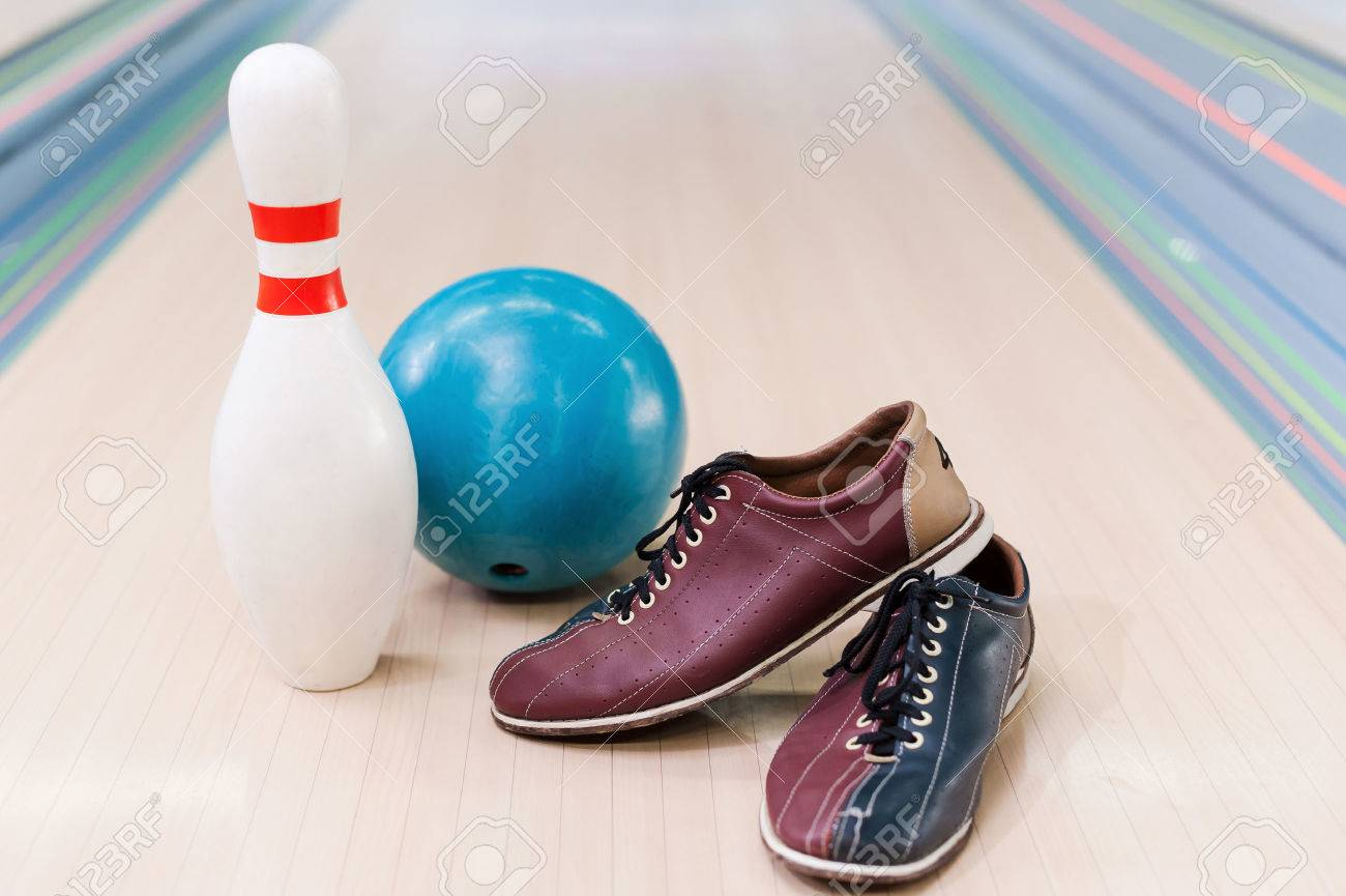 Close up of bowling shoes, blue ball and pin lying on bowling..