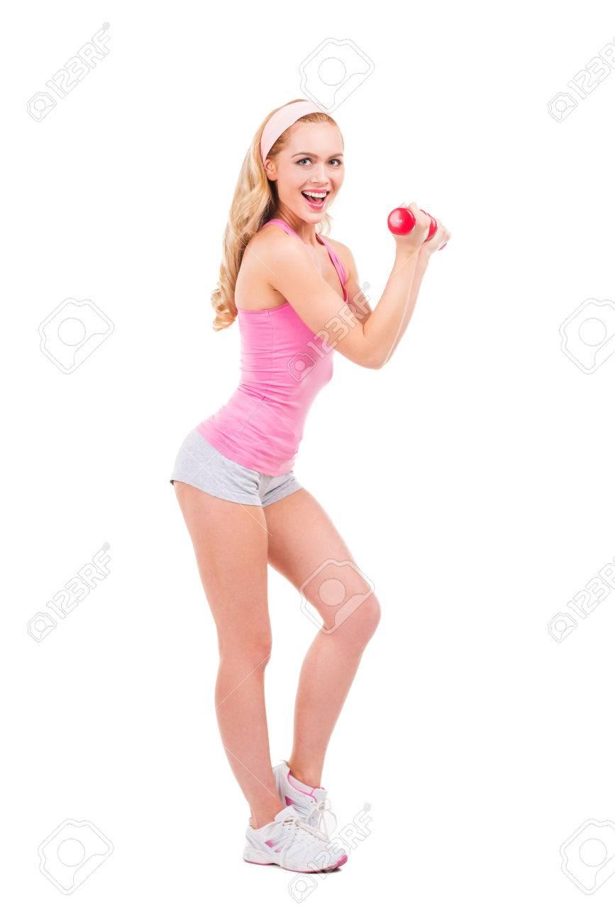 J'aime les sports! Longueur de belle pin up blonde cheveux femme en chemise rose exercice avec des haltères et souriant tout debout isolé sur fond