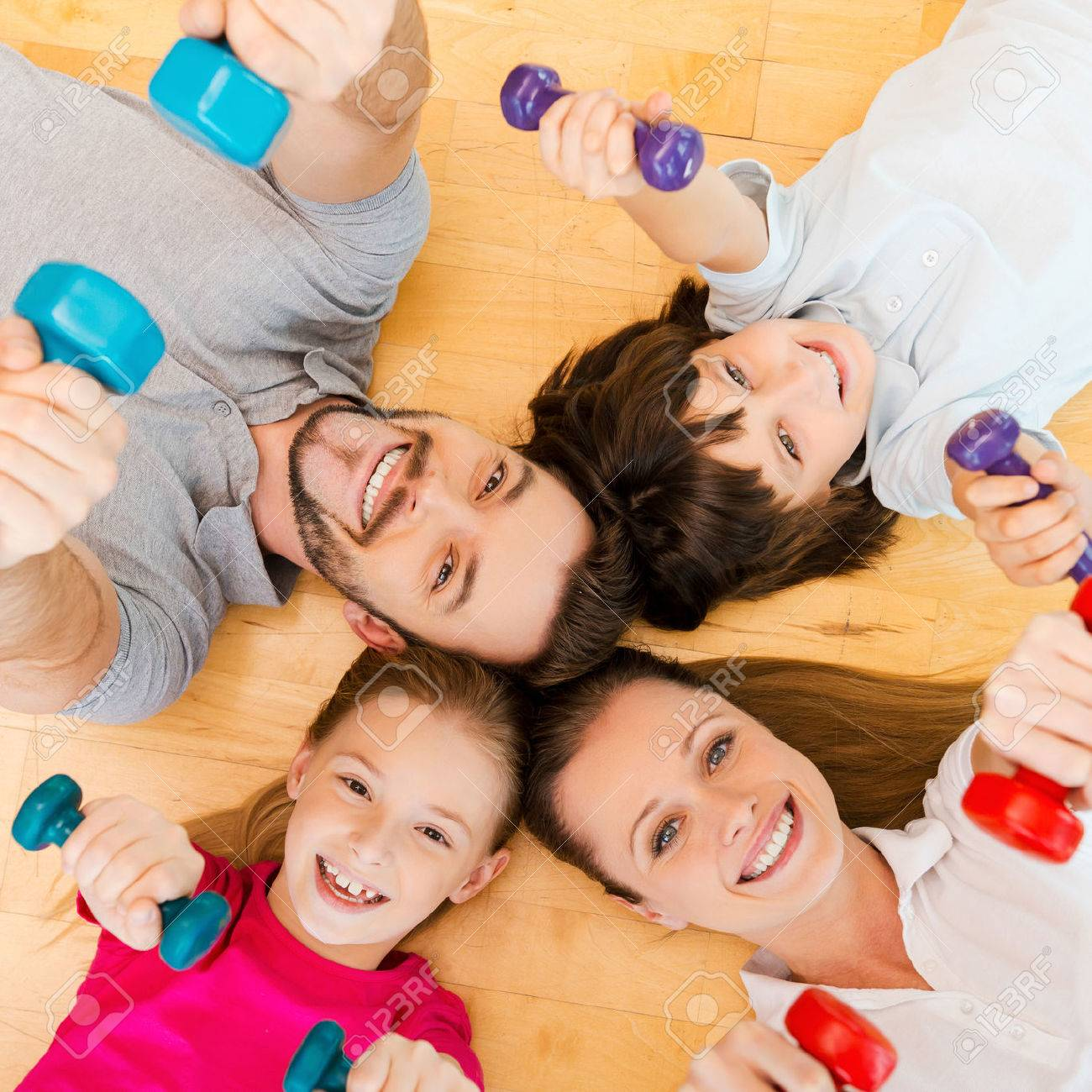 Living an active life. Top view of happy sporty family bonding to each other while lying on the floor and holding dumbbells - 37824317