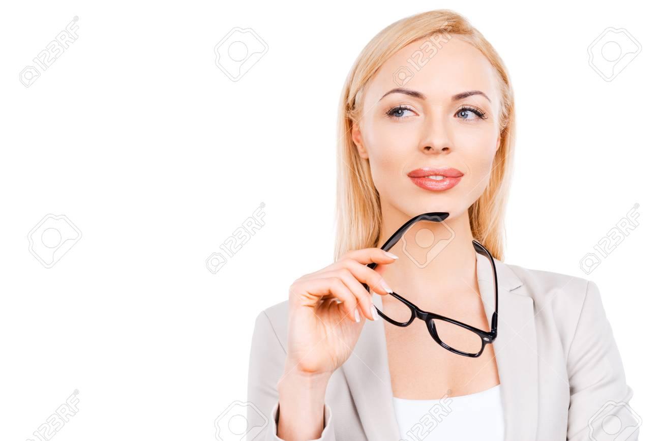 08f4d5575e Pensativa empresaria madura la celebración de las gafas y mirando a otro  lado mientras está de pie contra el fondo blanco