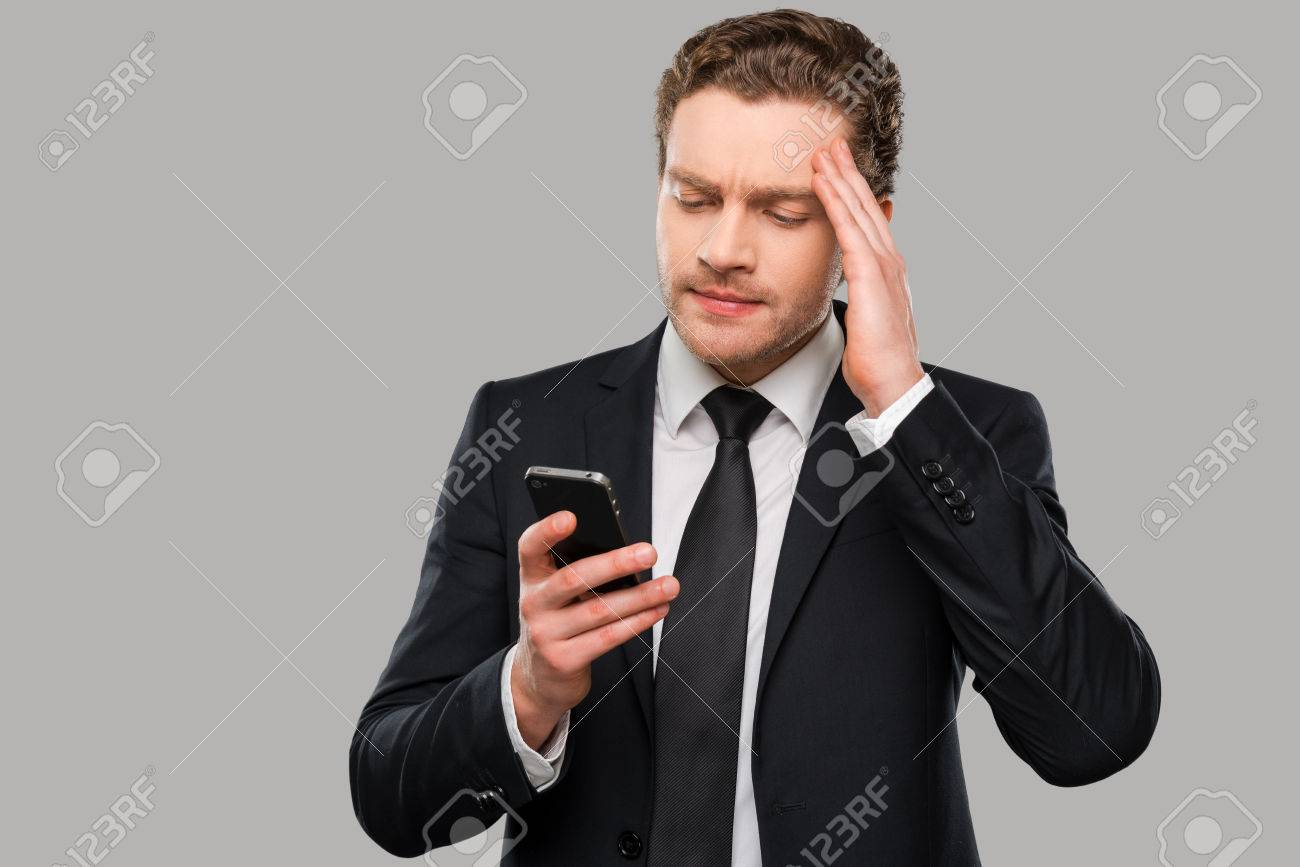 Frustrated office worker on the phone holding stock photo image - Frustrated Young Man In Formalwear Holding Mobile Phone And Touching Head With Hand