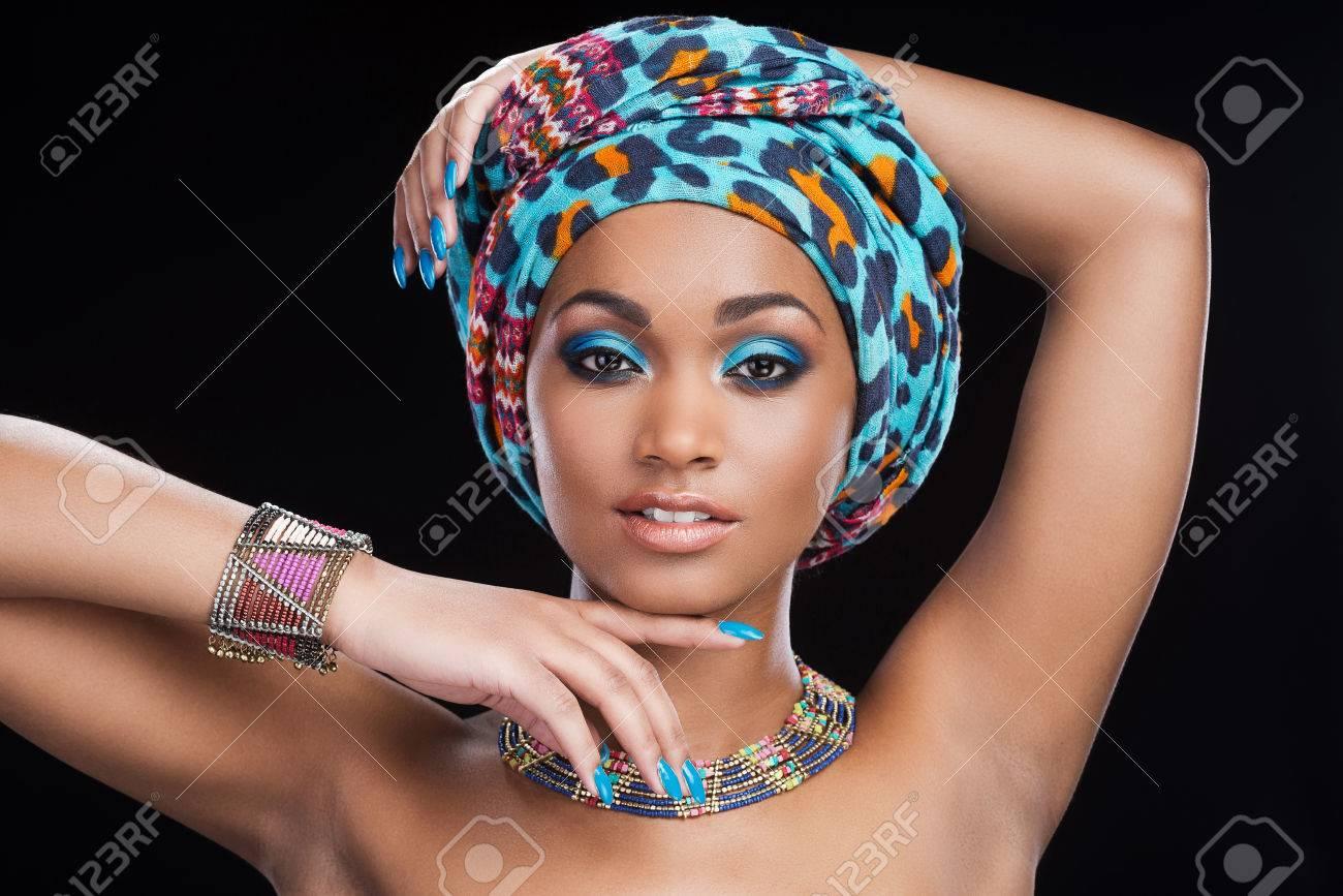 joli design dernière collection nouvelle qualité Dans un style traditionnel africain. Belle femme africaine à foulard et des  bijoux posant sur fond noir et regardant la caméra