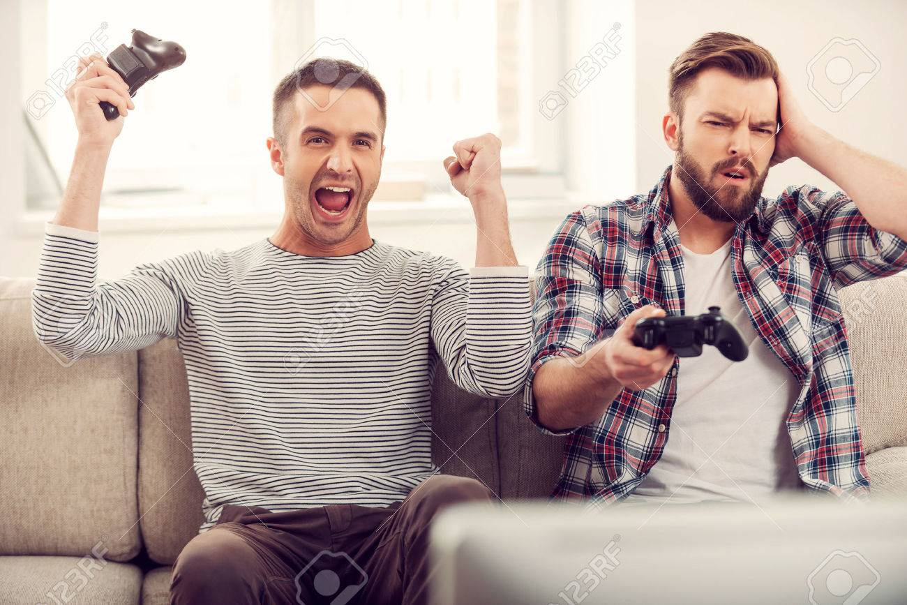 Friends and video games. Two handsome young men playing video games while  sitting on sofa