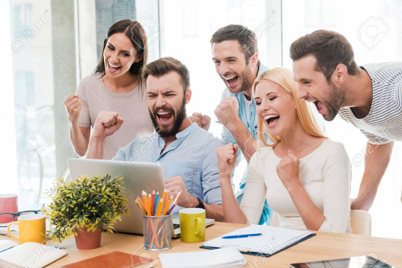 Everyday winners. Group of happy business people in smart casual wear looking at the laptop and gesturing Stock Photo - 41179586