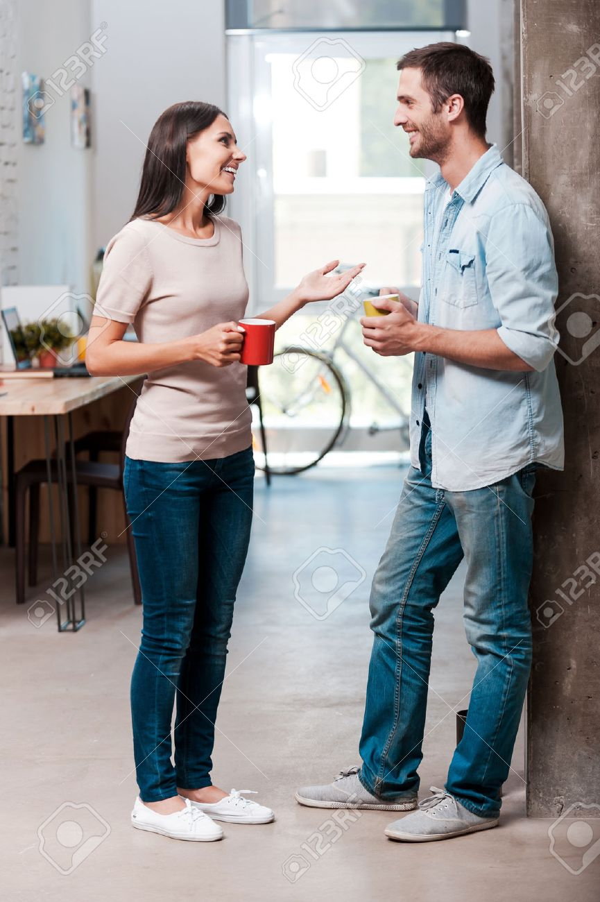 Coffee break. Full length of two cheerful young people talking and smiling during a coffee break in office Stock Photo - 41229615