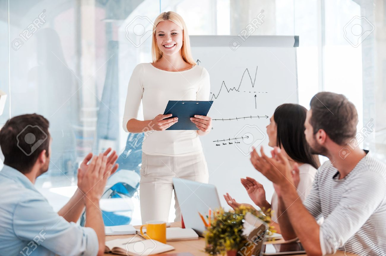 Great presentation! Cheerful young woman standing near whiteboard and smiling while her colleagues sitting at the desk and applauding - 41179606