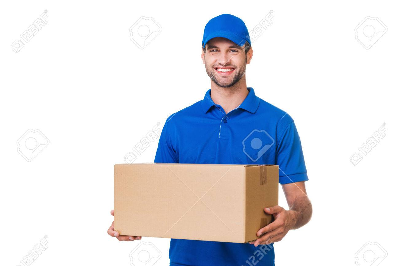 Cheerful delivery man. Happy young courier holding a cardboard box and smiling while standing against white background - 42055022