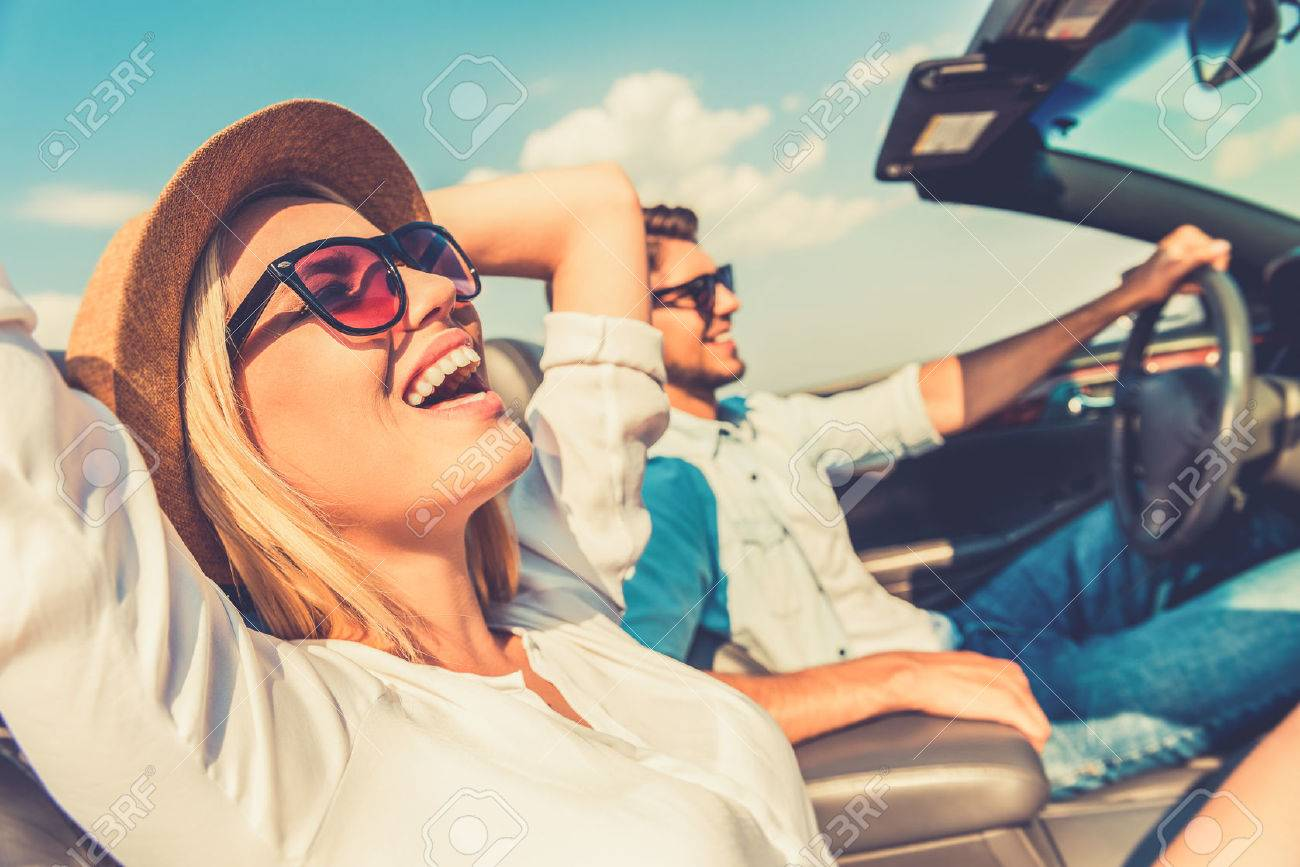Freedom of the open road. Side view of joyful young woman relaxing on the front seat while her boyfriend sitting near and driving their convertible Stock Photo - 42530509