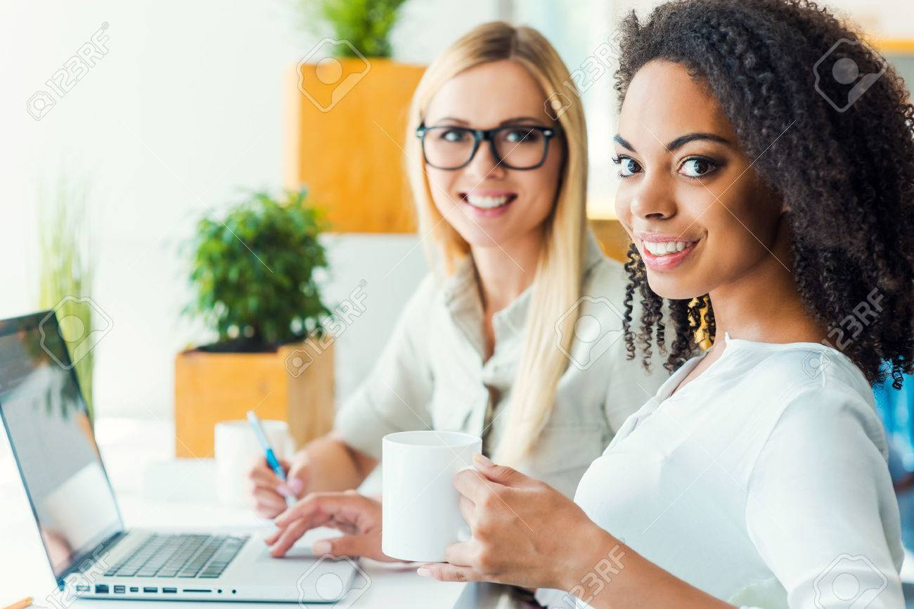 Two minds are better than one. Two smiling young women looking at camera and smiling while sitting at working place - 43053536