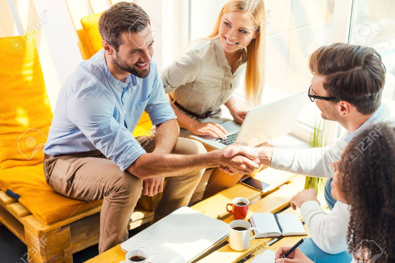 Congratulations! Two cheerful young men sitting at the wooden desk in office and shaking hands while two beautiful women looking at them and smiling - 43008677