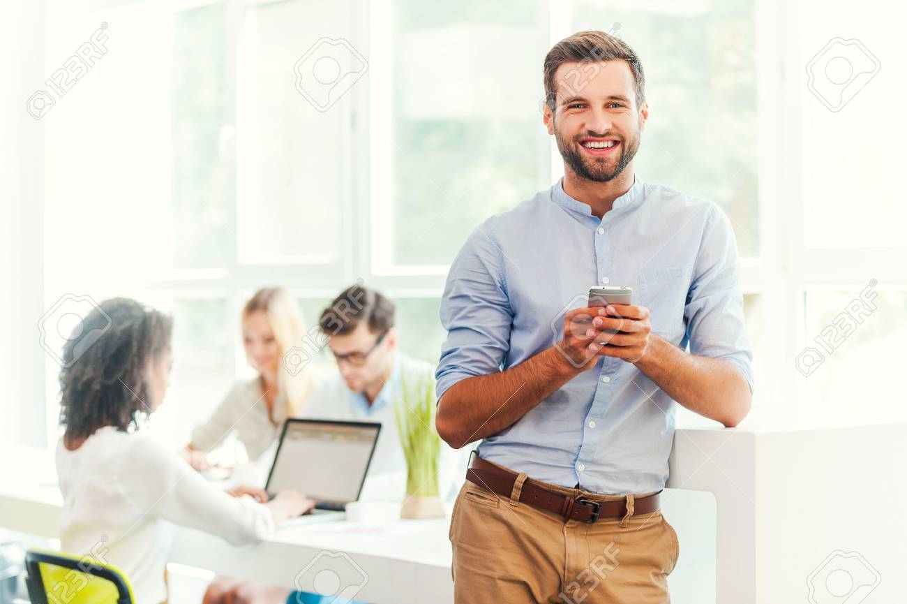 Enjoying Office Life Joyful Young Man Holding Mobile Phone And