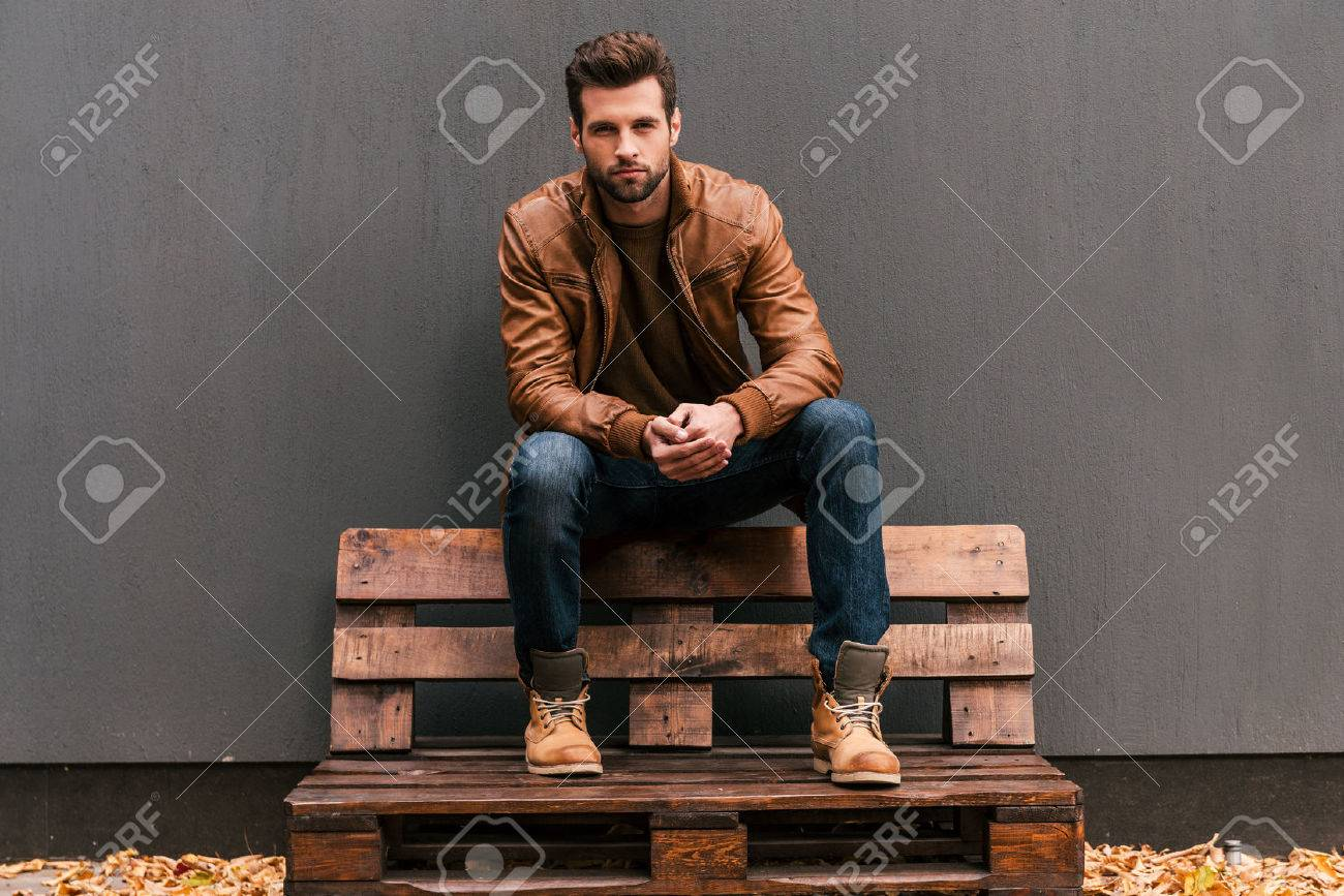 Confident and handsome. Handsome young man sitting on the wooden pallet and looking at camera with grey wall in the background and orange fallen leaves on the floor Stock Photo - 45974519