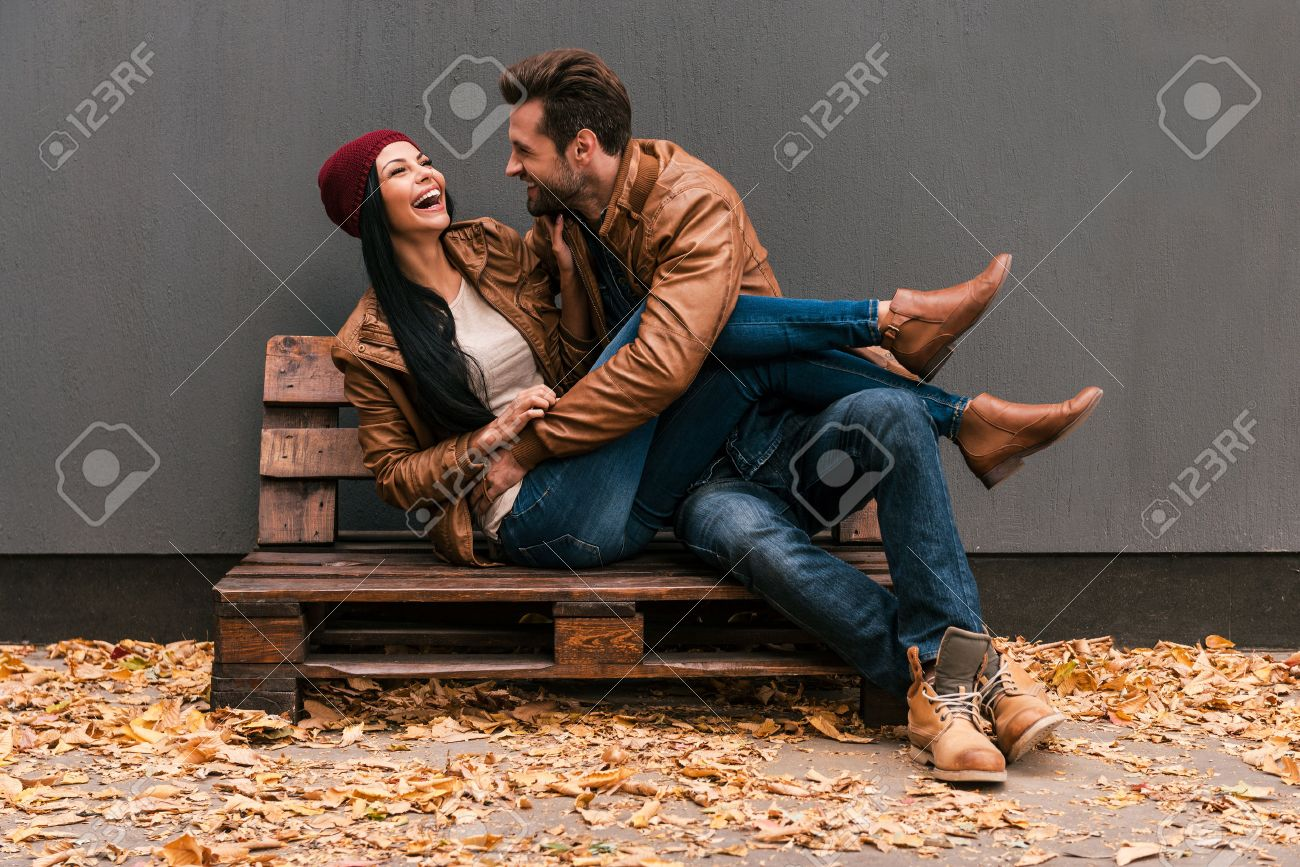 Carefree time together. Beautiful young couple having fun together while sitting on the wooden pallet together with grey wall in the background and fallen leaves on ht floor Stock Photo - 45974527