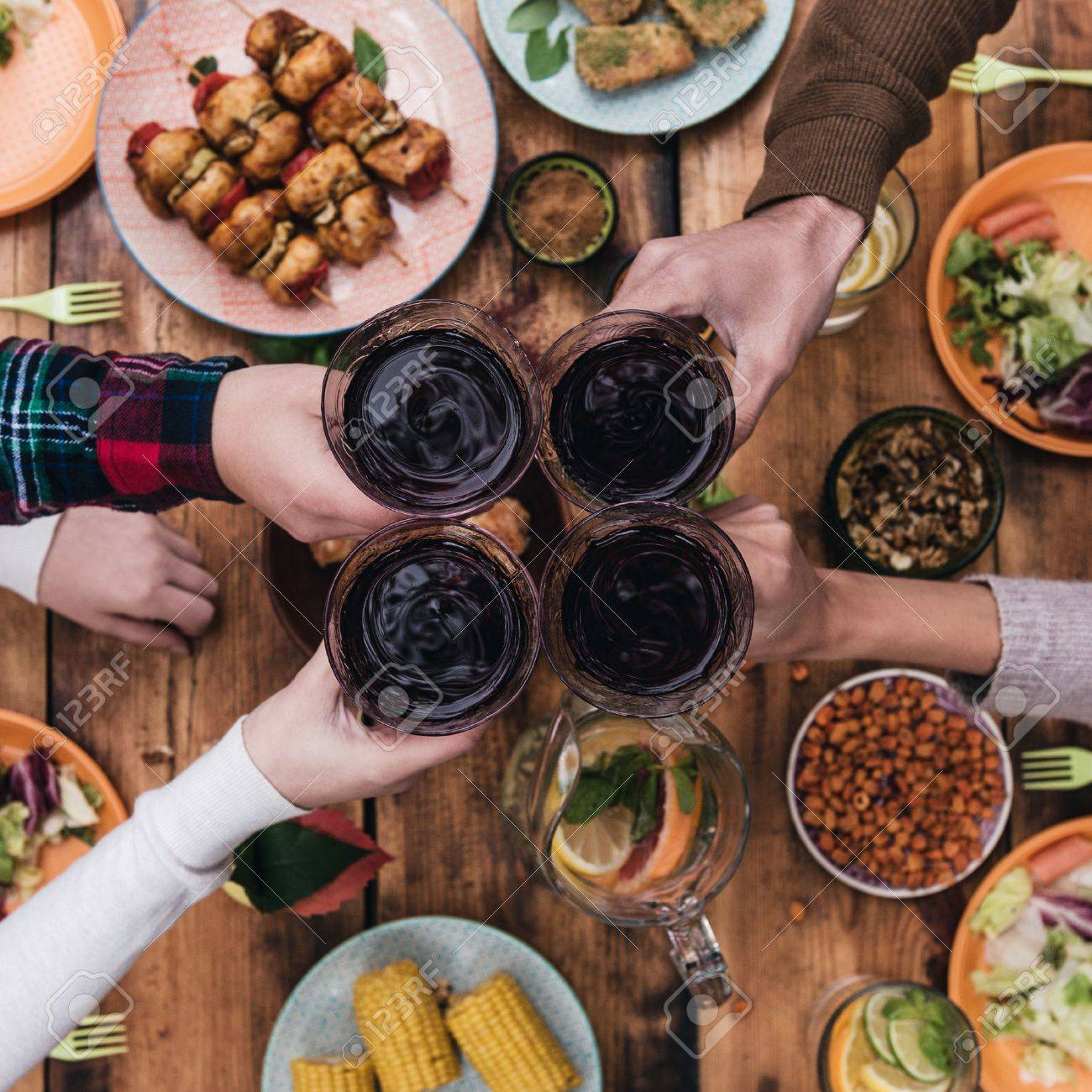 Dining Table Cheers To Friends Top View Of Four People Cheering With Red Wine While Sitting At