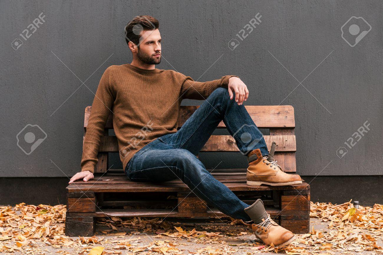 e4768a2021b654 Lässig schön. Hübscher junger Mann sitzt auf der Holzpalette und Wegschauen  mit grauer Wand im