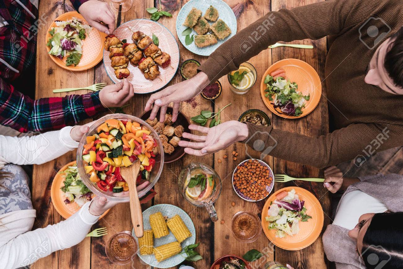 Friends having dinner. Top view of four people having dinner together while sitting at the rustic wooden table Stock Photo - 45974538