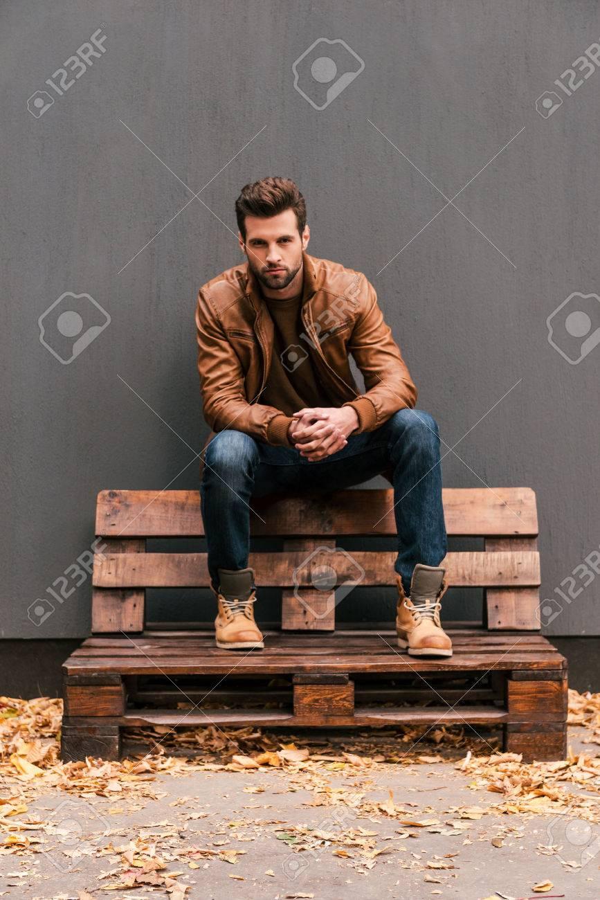 5db2668a4fbbed Lässig schön. Hübscher junger Mann sitzt auf der Holzpalette und auf Kamera  mit grauen Wand