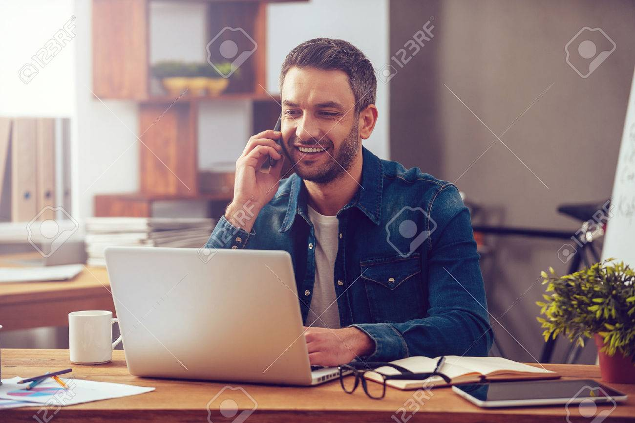 Enjoying good working day. Confident young man working on laptop and talking on the mobile phone while sitting at his working place in office Stock Photo - 48758912
