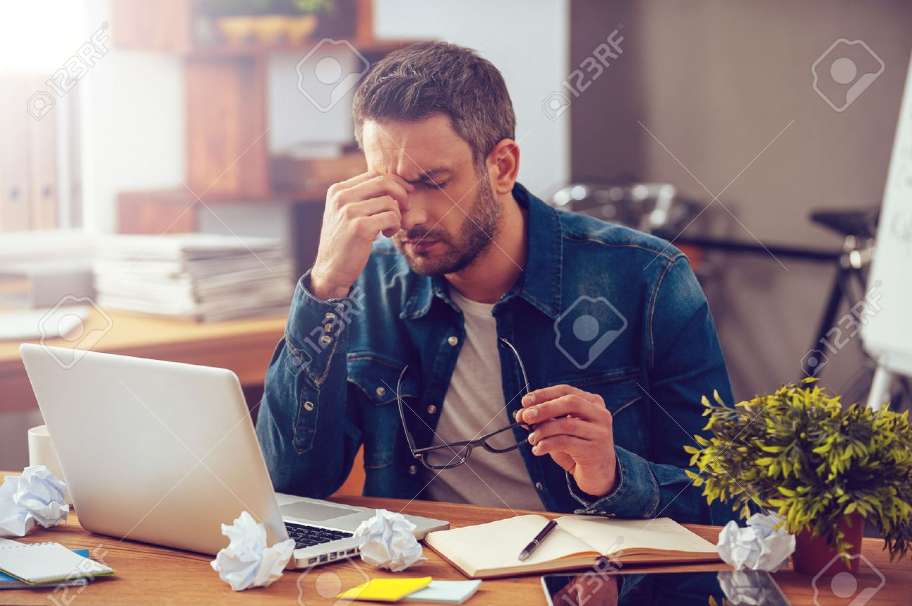 Frustrated office worker on the phone holding stock photo image - Frustration Feeling Sick And Tired Frustrated Young Man Massaging His Nose And Keeping Eyes
