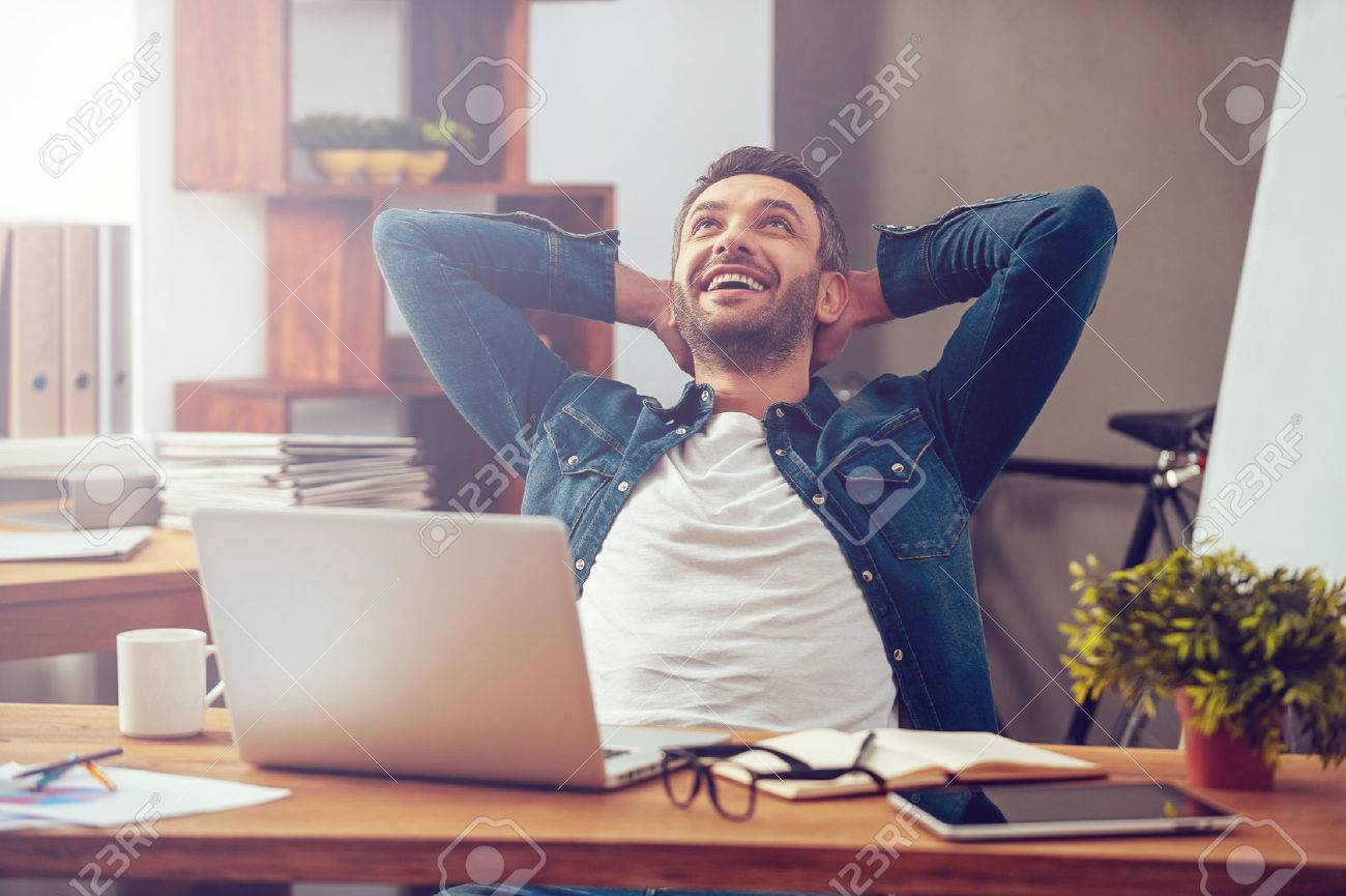 Satisfied with work done. Happy young man working on laptop while sitting at his working place in office Stock Photo - 48759298