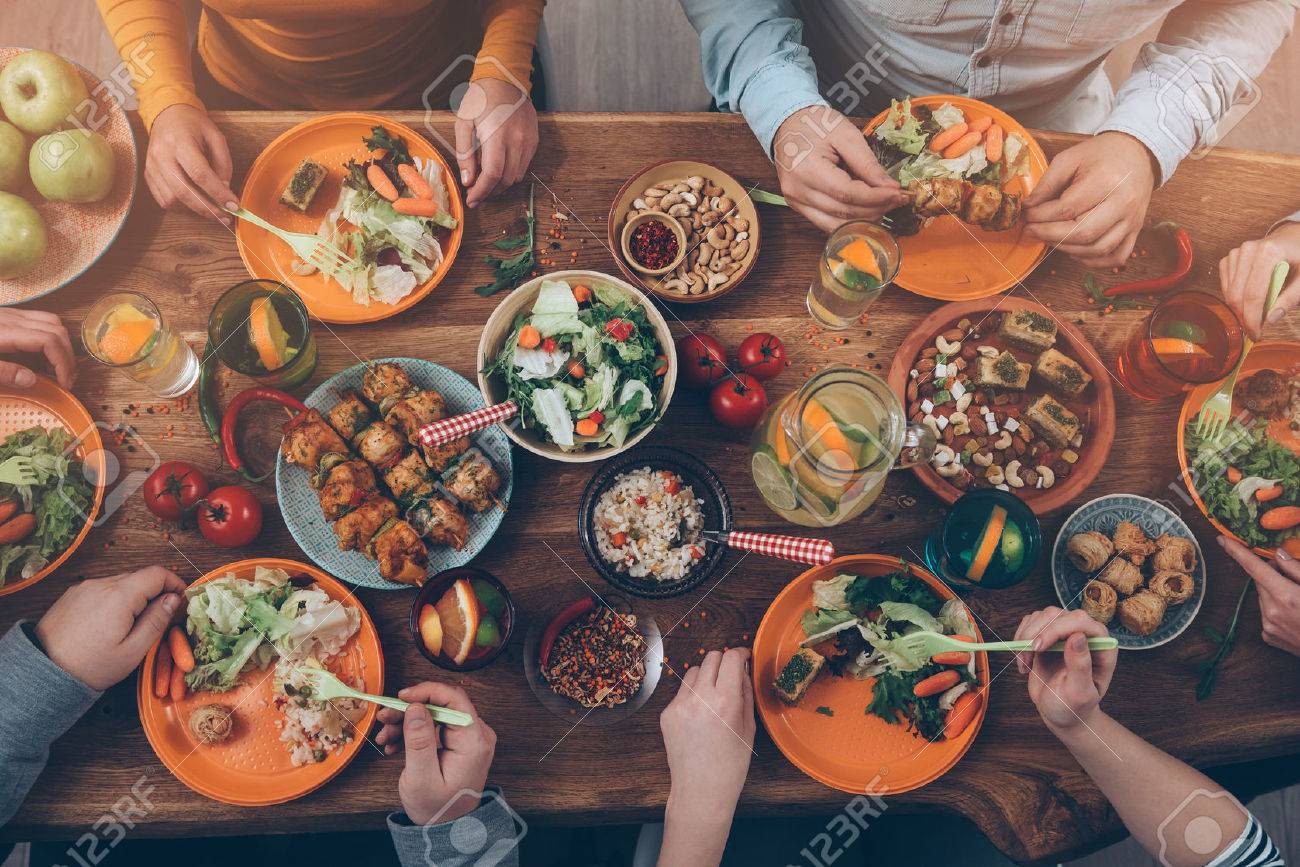 Enjoying dinner with friends. Top view of group of people having dinner together while sitting at the rustic wooden table Stock Photo - 49263818