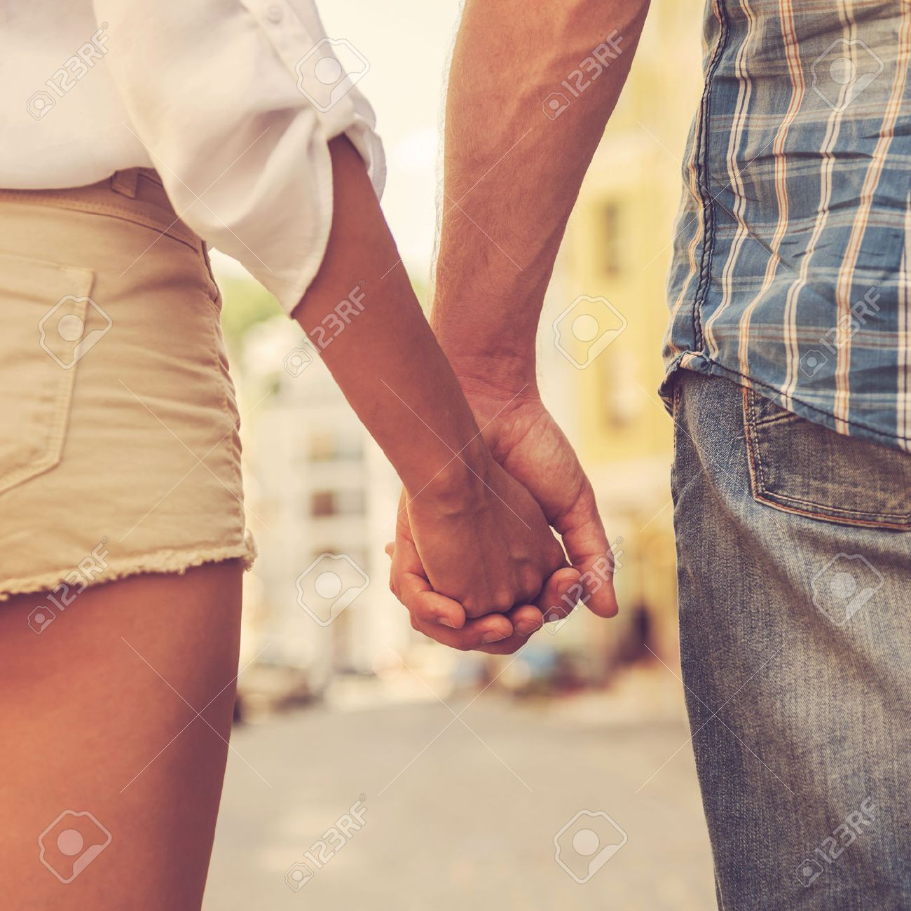 Hands and hearts together. Close-up of loving couple holding hands while walking outdoors Stock Photo - 51259721