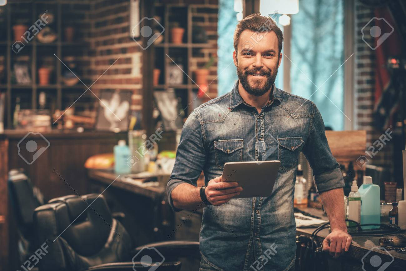 Keeping business on top with digital technologies. Cheerful young bearded man looking at camera and holding digital tablet while standing at barbershop - 51259656