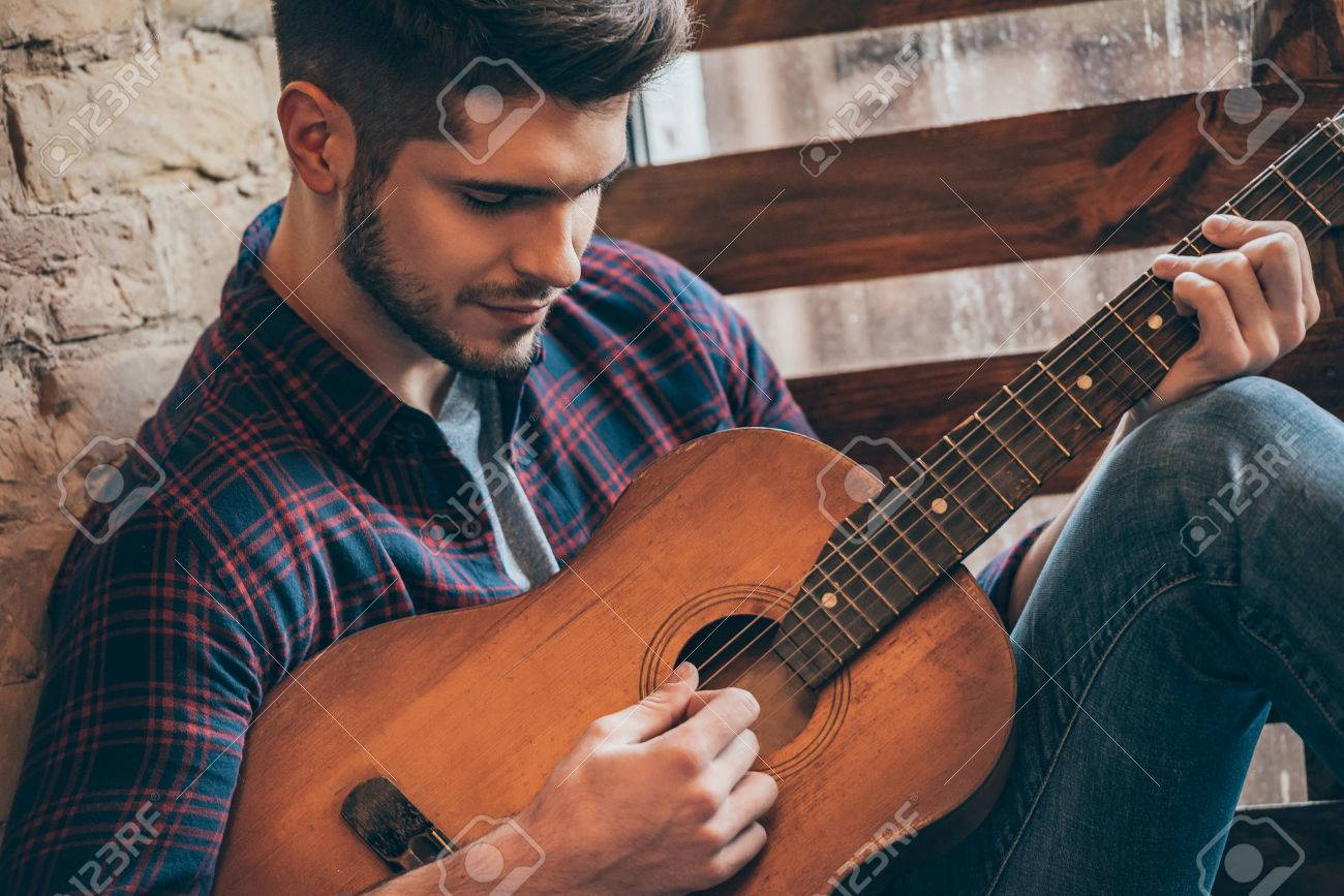Perfect Chord Close Up Of Handsome Young Man Playing Guitar Stock