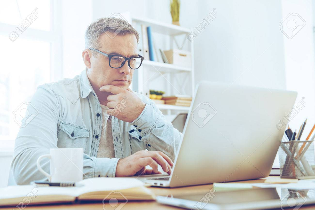 Confident and concentrated. Thoughtful mature man looking at his laptop and keeping hand on chin while sitting at his working place - 53602113