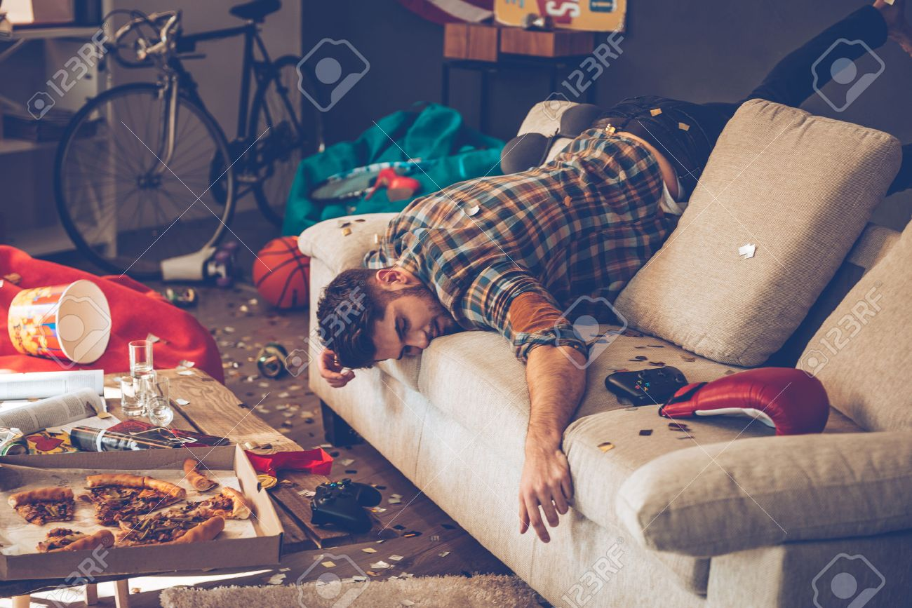 Young handsome man passed out on sofa in messy room after party Banque d'images - 54360556
