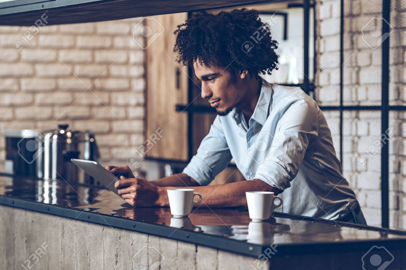 Side view of young African man using his digital tablet while leaning at bar counter with two coffee cups - 54361086