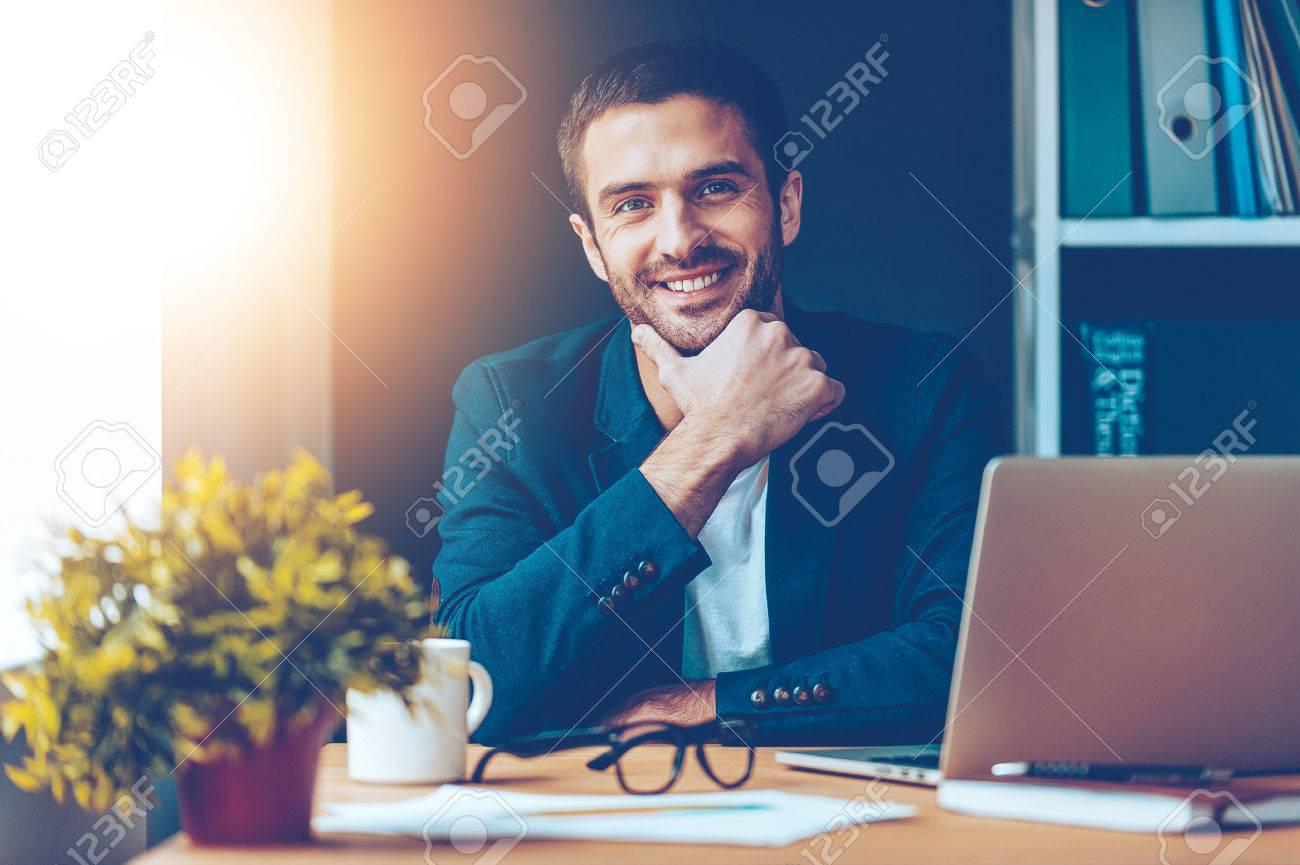 Confiant et beau. Confiant jeune homme tenant la main sur le menton et souriant alors qu'il était assis sur son lieu de travail dans le bureau Banque d'images - 54625118