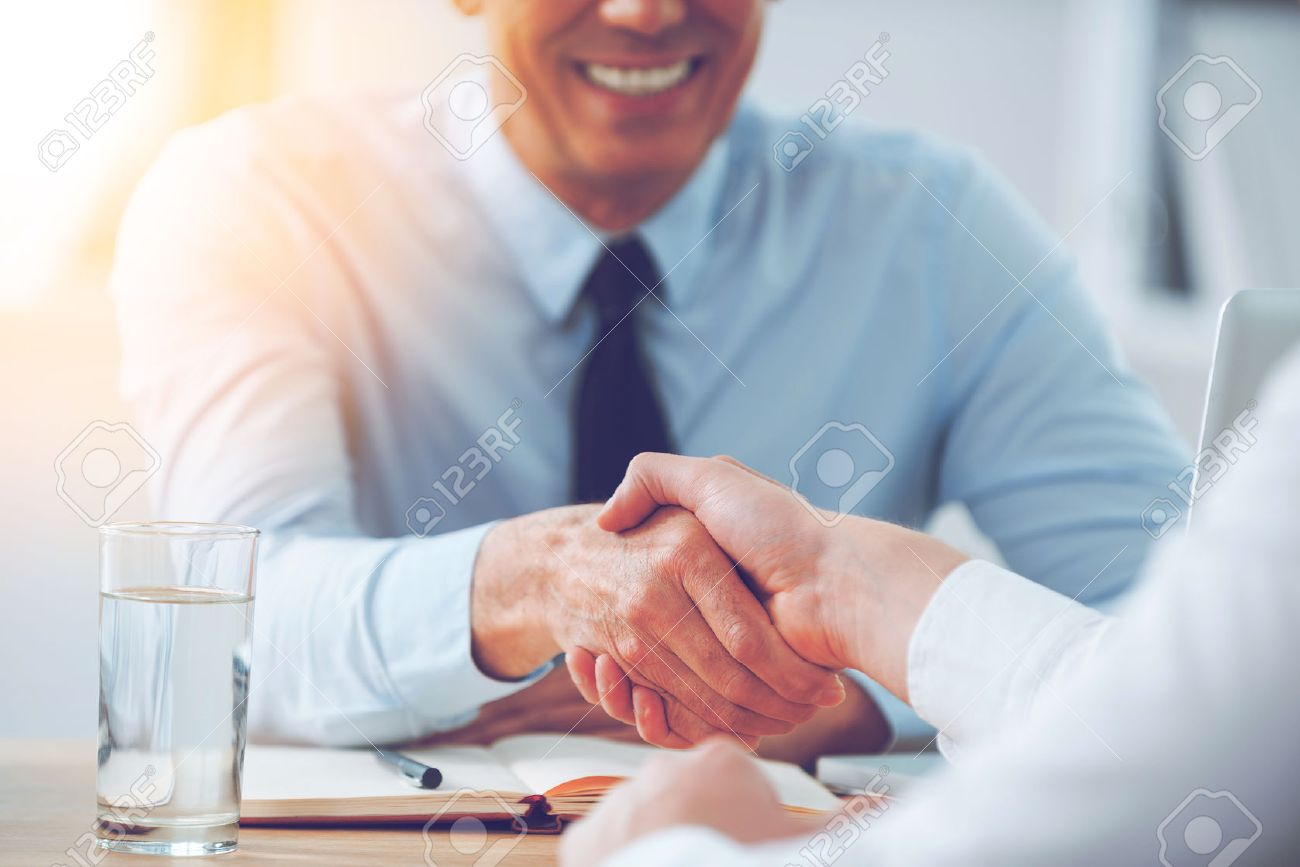 Good deal. Close-up of two business people shaking hands while sitting at the working place Banque d'images - 54625309