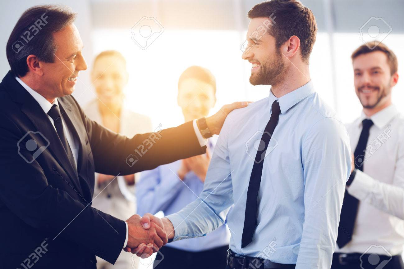 Great job! Two cheerful business men shaking hands while their colleagues applauding and smiling in the background Banque d'images - 54625316