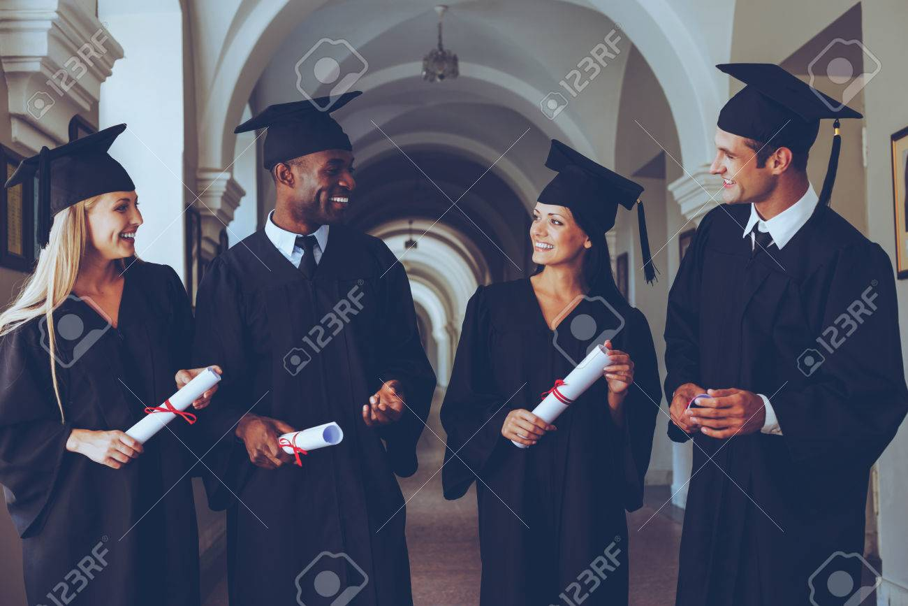 happy to be graduated four college graduates in graduation gowns happy to be graduated four college graduates in graduation gowns walking along university corridor and