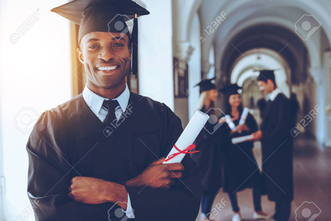 Happy Graduate. Happy African Man In Graduation Gowns Holdin Stock ...