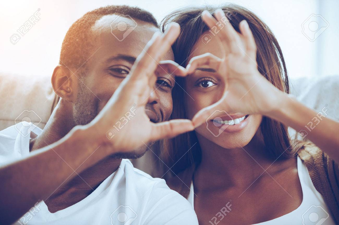 Love is in the air! Beautiful young African couple sitting close to each other and looking through a heart shape made with their fingers Banque d'images - 54727966