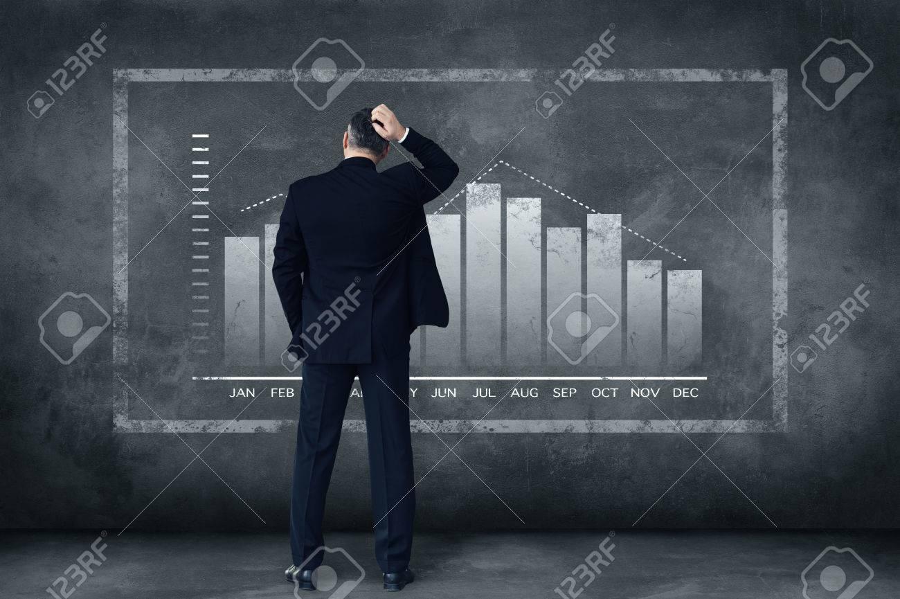 Des décisions difficiles chaque jour. Vue arrière d'affaires d'âge mûr se gratter la tête en se tenant debout sur fond gris avec l'illustration de graphique Banque d'images - 54885083