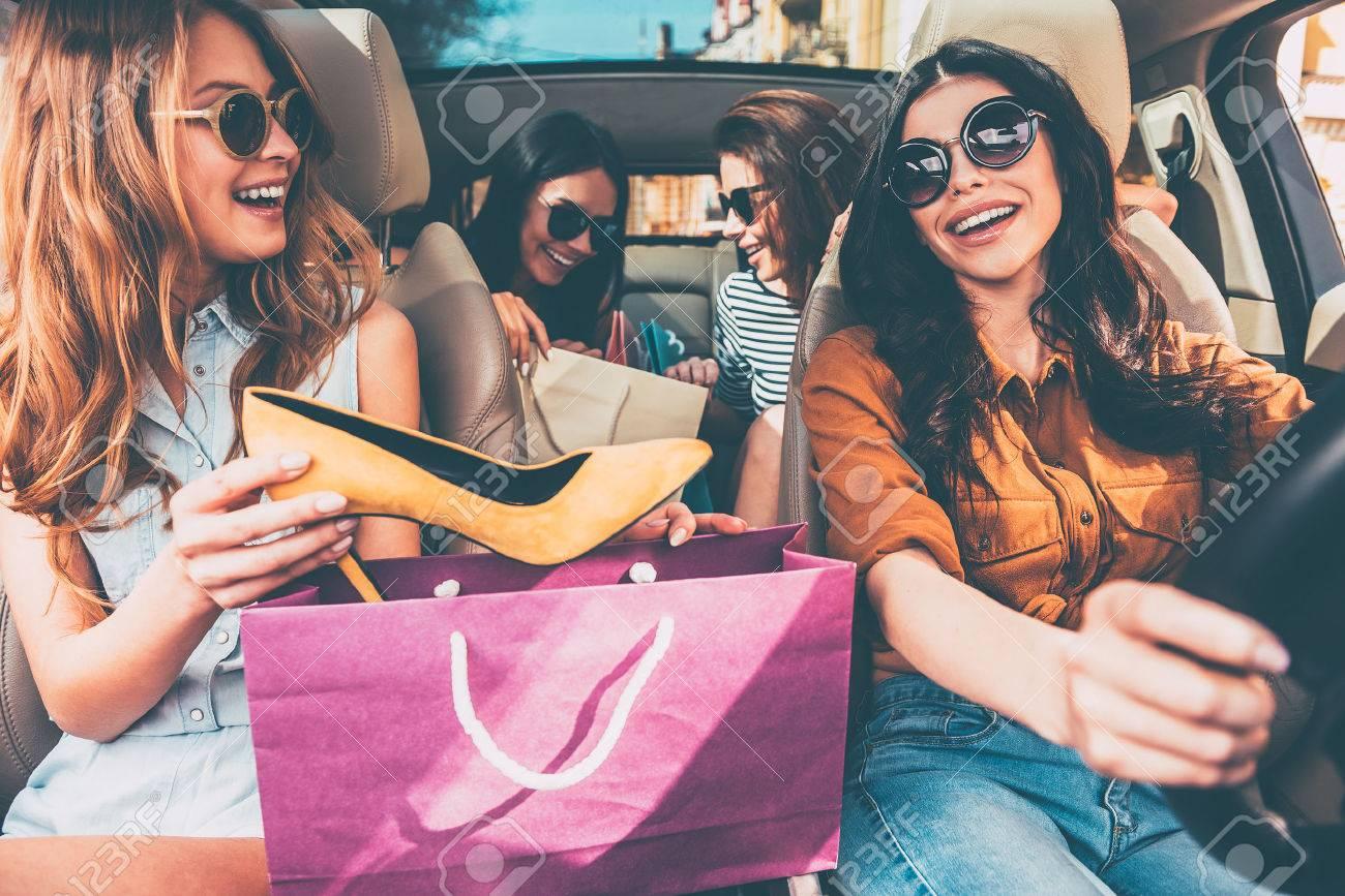 Le prochain arrêt est vendeuse de lingerie! Quatre belles jeunes femmes gaies tenant des sacs et en regardant les uns les autres avec le sourire alors qu'il était assis dans la voiture Banque d'images - 55235195