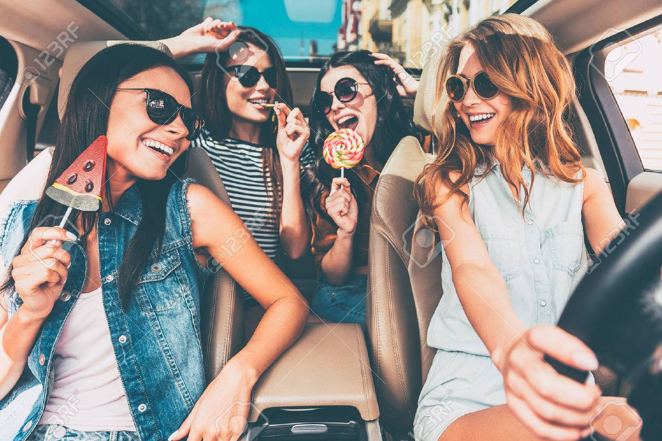 Great start of their journey. Four beautiful young cheerful women looking at each other with smile and holding lollipops while sitting in car Banque d'images - 55235201