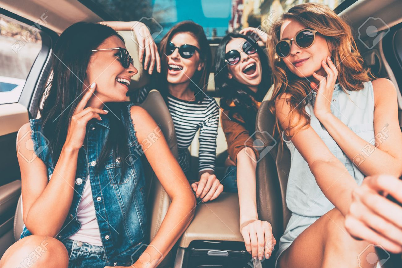 Enjoying road trip together. Four beautiful young cheerful women looking happy and playful while sitting in car Banque d'images - 55235232