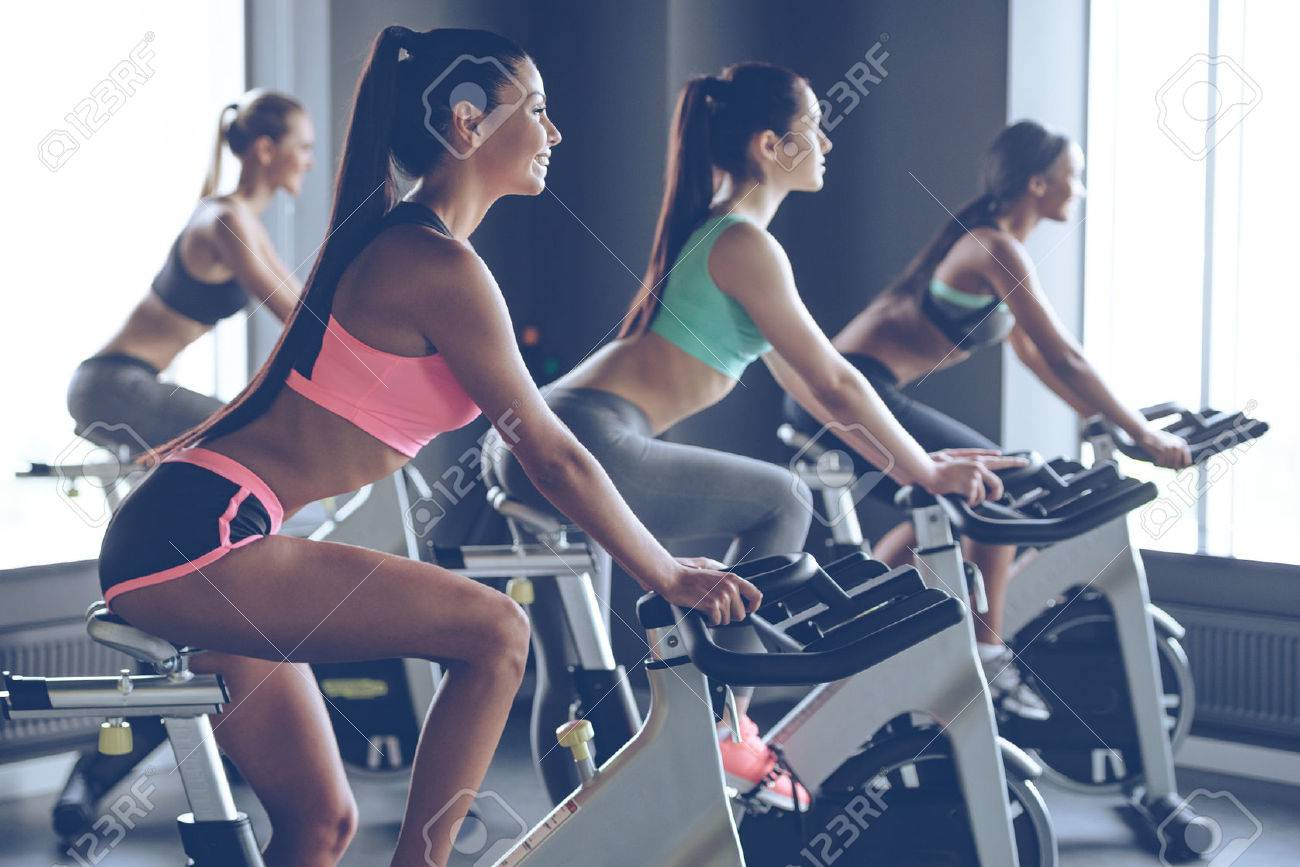 Beautiful ride. Side view of young beautiful women with perfect bodies in sportswear looking away with smile while cycling at gym Banque d'images - 55863408