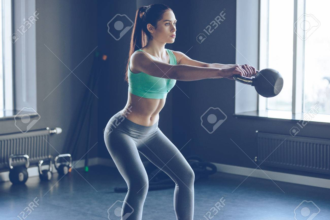 formation croisée parfaite. Vue de côté de la belle jeune femme avec un corps parfait de vêtements de sport de travail avec une bouilloire cloche à une salle de sport Banque d'images - 55863419