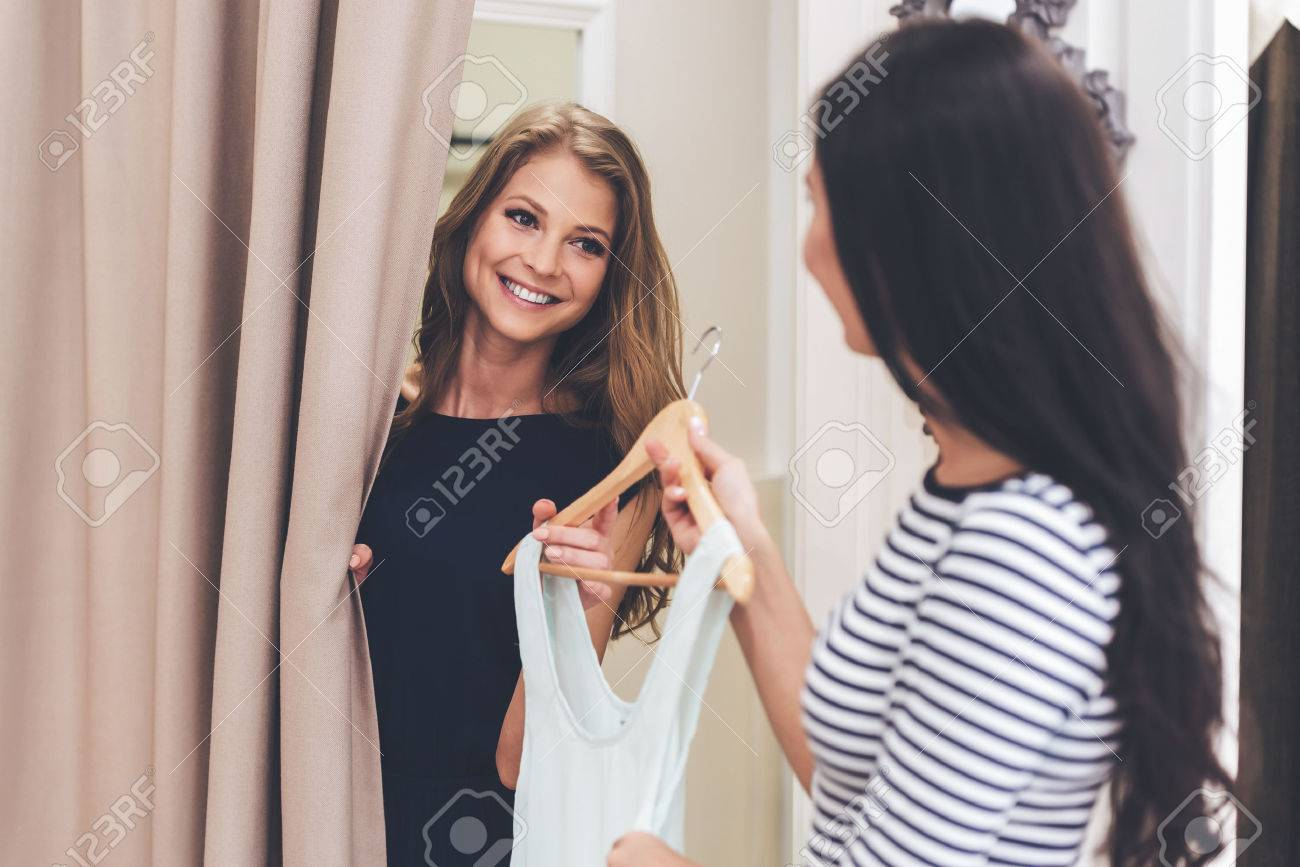 You should try on this dress! Beautiful young woman taking dress on hanger from seller while standing in fitting room at the store Banque d'images - 57175542
